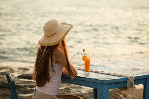 Young fit woman in summer outfit seating on wooden blue chair bu