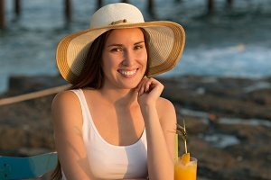 Beautiful smiling young woman seating in cafe by seaside with or