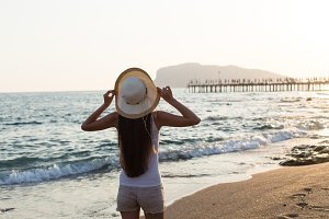 Young fit woman wearing straw hat by seaside