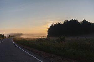 misty road through green fields
