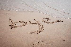 Bye written on sand