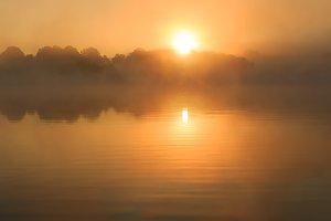 Orange sun rising over lake France