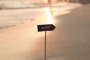 Vacation or holidays concept - beach sign and sunset