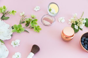 Cosmetics with flowers on pink