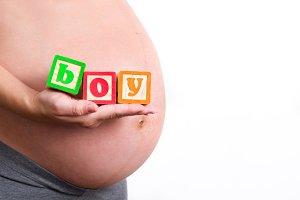 "Pregnant woman holding ""boy"" word"