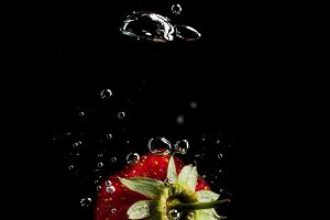 Strawberry droped into the water