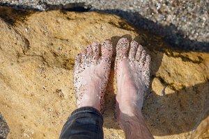 Seashells and sand on their feet
