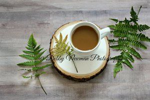 Coffee and ferns on wood
