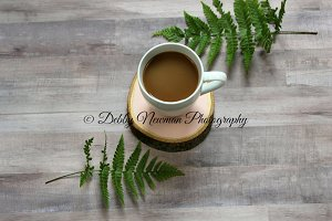 Coffee cup on pink wood with ferns
