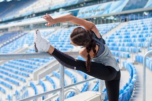Young sporty girl with a tanned skin makes a banner in the stadium. The woman pulls the leg up, making the warm-up