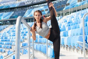 Young sporty girl doing workout at the stadium. She raised her leg up over head. Woman in sportswear a great stretch