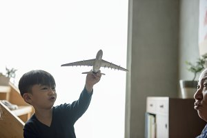 Cheerful boy playing toy plane