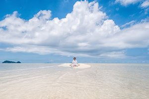 Young man meditating in lotus position on the beautiful long beach with clouds background.