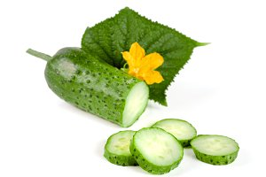 Sliced cucumber with leaf and flower isolated on a white background
