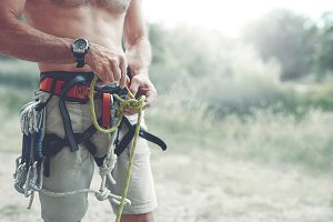 A man Knots a knot on a climbing harness