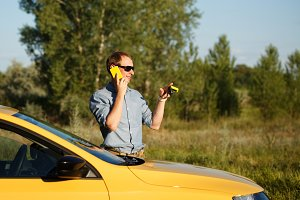 Man talking on phone at car
