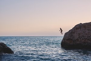 man jumping into the sea from the cliff