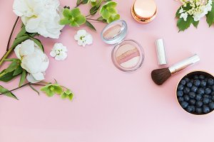Cosmetics and flowers on pink table