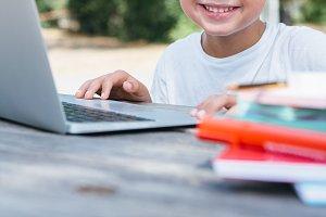 Unrecognizable smiling boy at laptop
