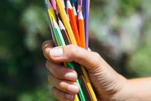 Hand holding colorful pencils