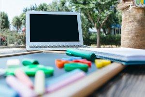 Laptop and blackboard in park