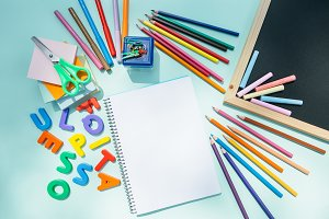 Colorful pencils and chalks on notepad