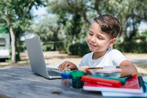 Boy with laptop in park