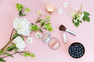 Cosmetic with flowers on pink table