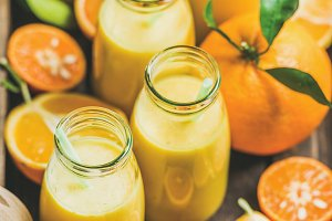 Healthy yellow smoothie in bottles