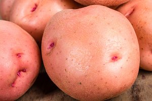 Red potatoes on wooden table