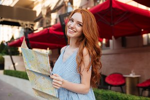 Happy pretty girl with long red hair holding map
