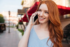 Smiling attractive girl with long hair talking on mobile phone