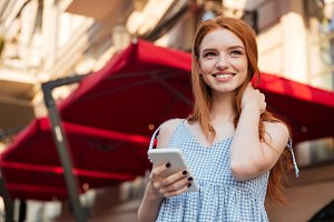 Smiling young redhead girl holding mobile phone
