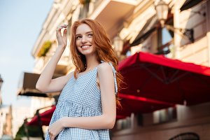 Smiling redhead girl standing outside