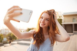 Smiling redhead girl with long hair taking a selfie