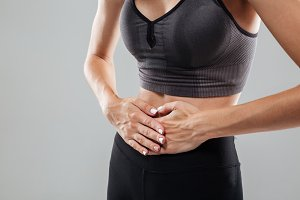 Cropped image of a woman holding hands on her belly