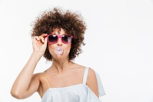 Positive young woman in sunglasses blowing bubbles