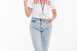 Happy volunteer woman wearing badge standing and showing ok gesture