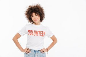 Young woman in volunteer shirt standing with hands on hips