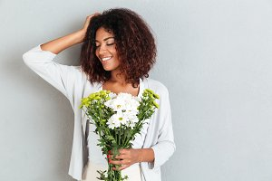 Lovely young african woman holding flower bouquet and smiling