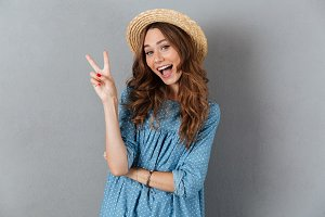 Smiling young pretty woman showing peace gesture