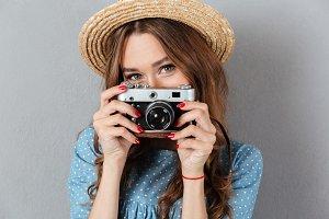 Caucasian woman photographer holding camera.