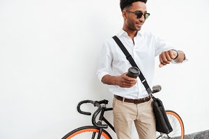 African man with bicycle drinking coffee.