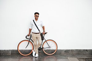 African man with bicycle standing over white wall