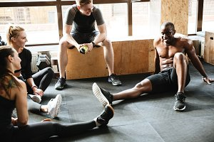 Group of sports strong people sitting in gym