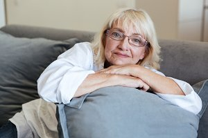Smiling mature lady sitting on a couch