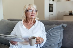 Mature woman in eyeglasses holding newspaper