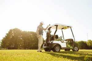 Golfer taking clubs from a bag in a golf cart