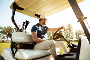 Male golfer driving a cart with golf clubs bag