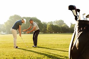 Young sportsman practicing golf with his teacher